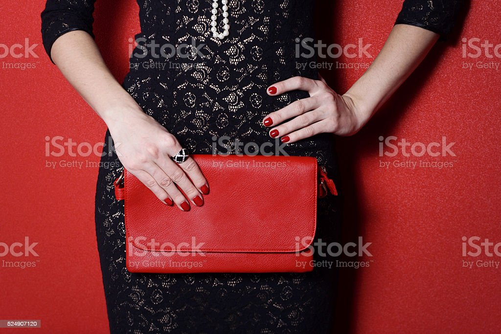 Fashionable woman with a red bag in her hands stock photo