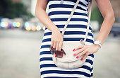 ファッショナブルな女性、バッグで手とストライプドレス