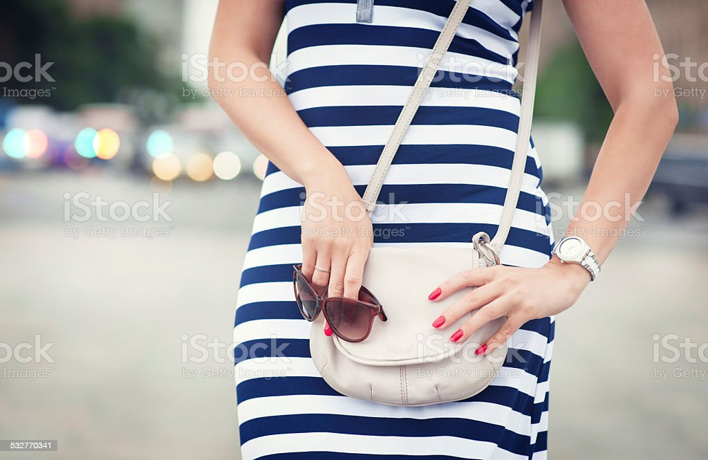 Fashionable woman with bag in her hands and striped dress stock photo