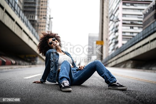 624206636istockphoto Fashionable Woman with Curly Hair at Street 972902466