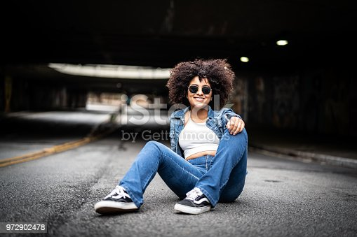 624206636istockphoto Fashionable Woman with Curly Hair at Street 972902478