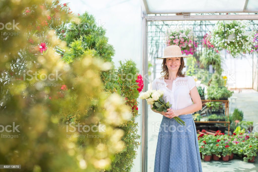 Fashionable woman with flowers in florist shop stock photo