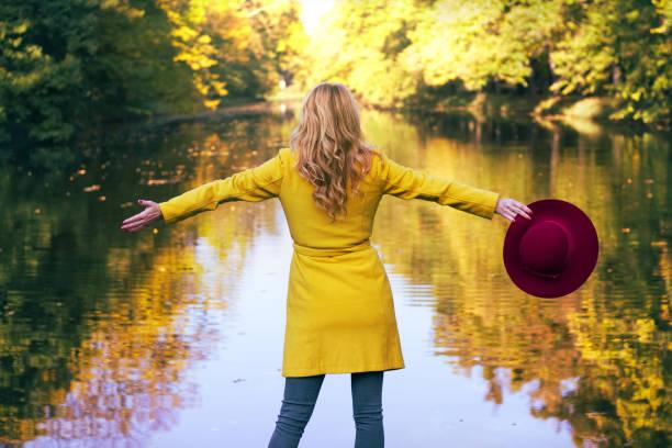 Femme à la mode avec chapeau rouge en parc public. Fille cheveux blonds jouit vue sur un lac à la saison d'automne. - Photo