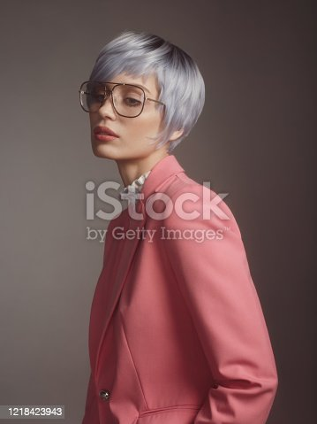 Portrait of beautiful fashionable woman with blue hair and pink blazer