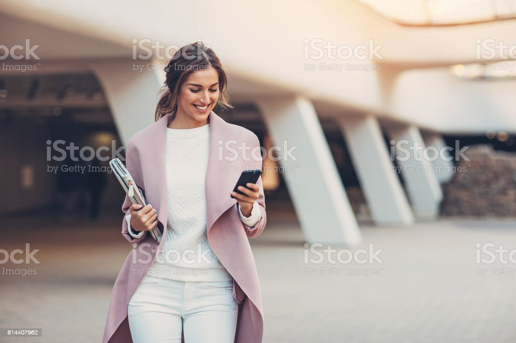 Fashionable woman with smart phone Elegant woman texting outdoors in the city Adult Stock Photo