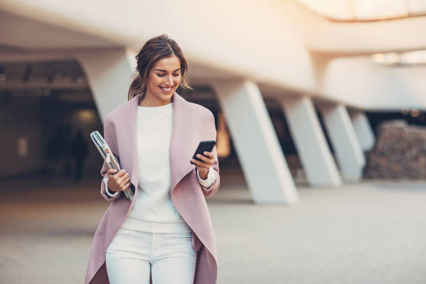 Fashionable woman with smart phone Elegant woman texting outdoors in the city grace stock pictures, royalty-free photos & images