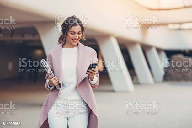 Elegant woman texting outdoors in the city
