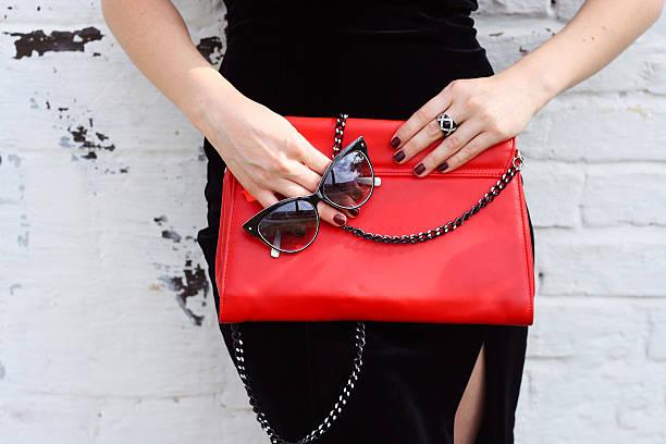 elegante modische frau mit roten kupplung und eine sonnenbrille mit - vintage bag stock-fotos und bilder