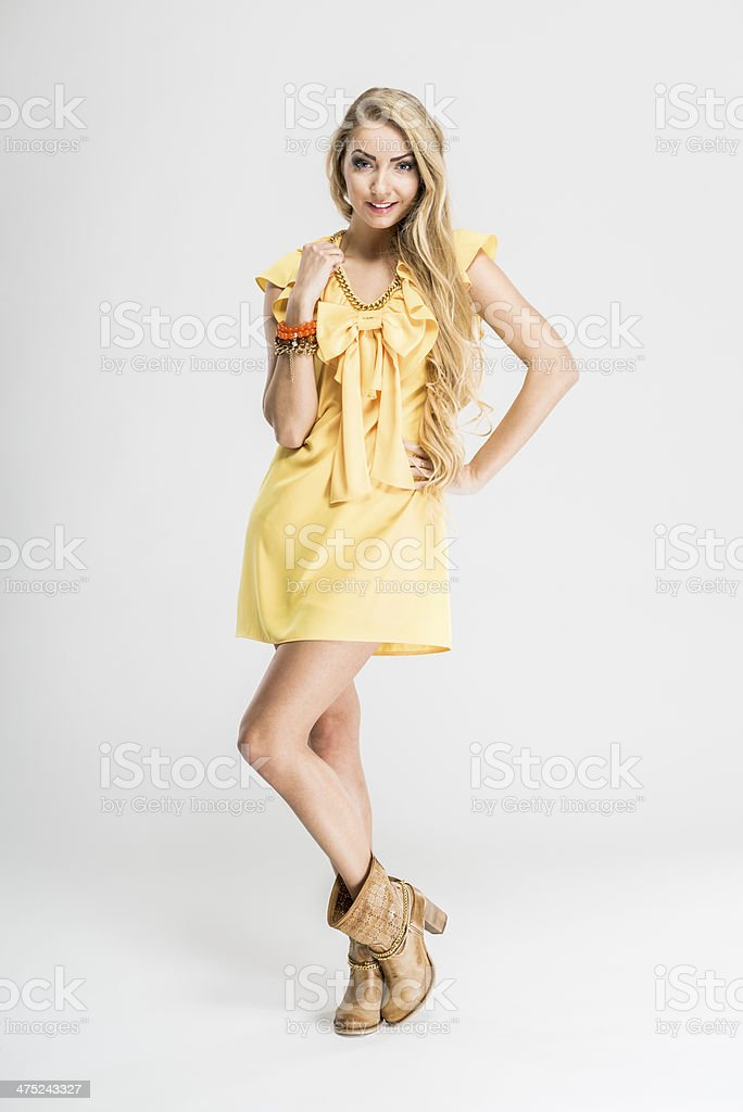 Fashionable woman's elegant sleeveless dress in yellow color, isolated stock photo