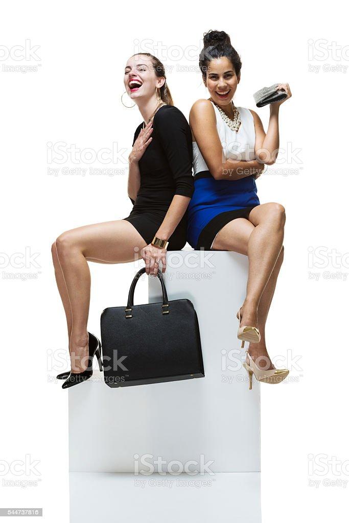 Fashionable women sitting on box stock photo