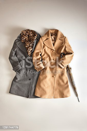 Fashionable women's coats on beige background (with clipping path)