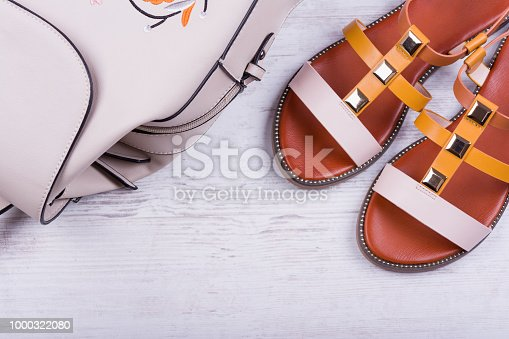 istock Fashionable women's sandals and backpack on white wooden background 1000322080