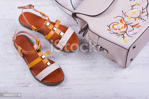 istock Fashionable women's sandals and backpack on white wooden background 1000322116