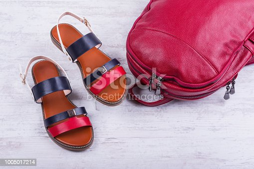 175597083 istock photo Fashionable women's sandals and backpack on white wooden background 1005017214