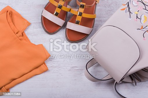175597083 istock photo Fashionable women's sandals and backpack on white wooden background 1008012084