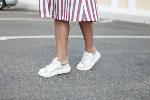 Fashionable women's white leather sneakers. Stylish women's shoes. Casual design. Close-up of female legs.