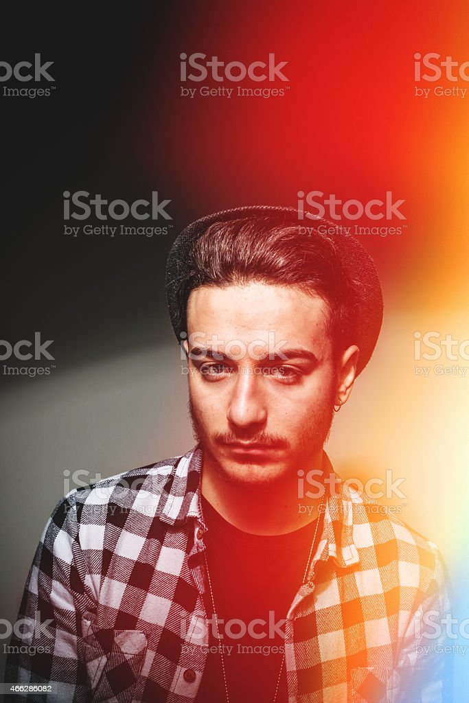 fashionable young adult posing on whie wall stock photo