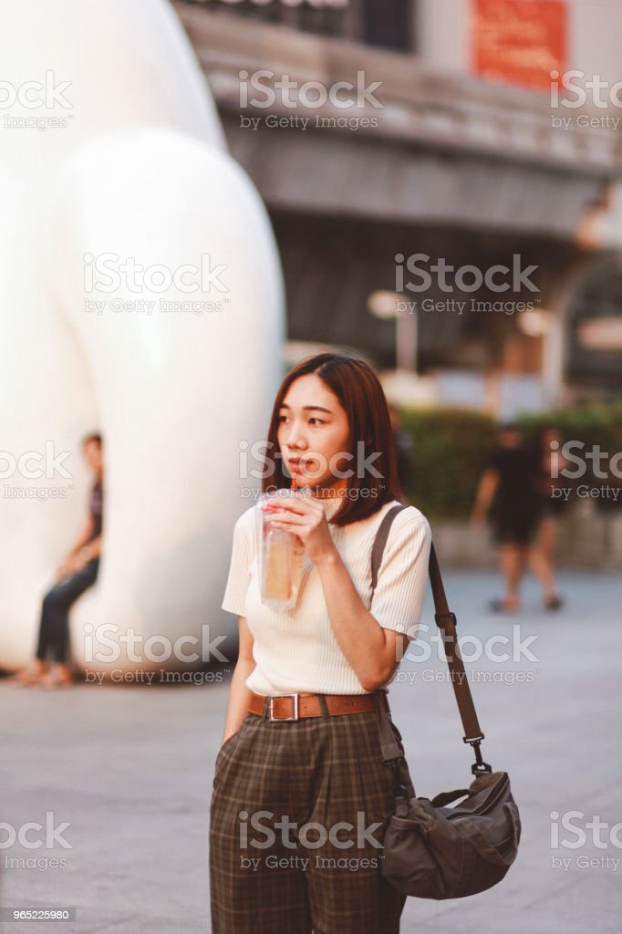 Fashionable young Asian woman walking in Bangkok downtown district royalty-free stock photo