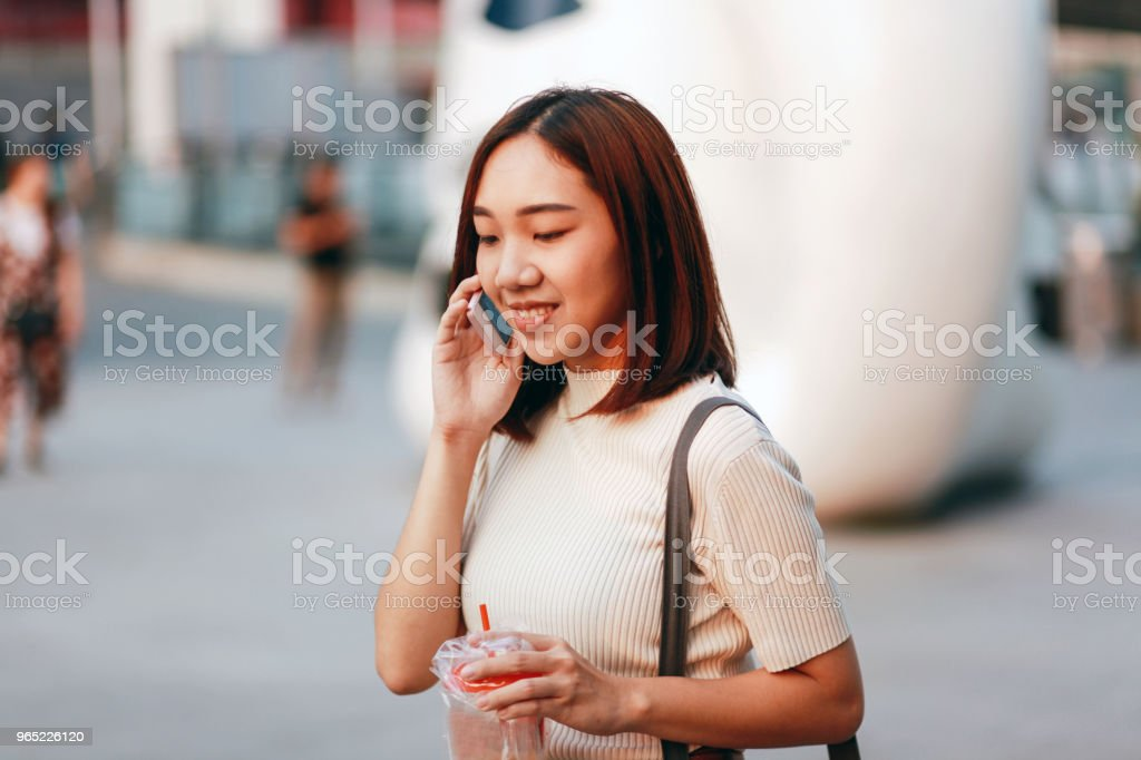 Fashionable young Asian woman walking in Bangkok downtown district, talking on the cellphone zbiór zdjęć royalty-free