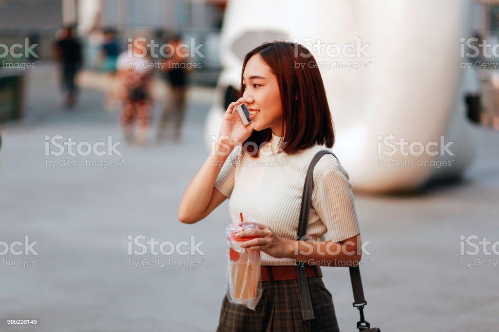 Fashionable young Asian woman walking in Bangkok downtown district, talking on the cellphone zbiór zdjęć royalty-free