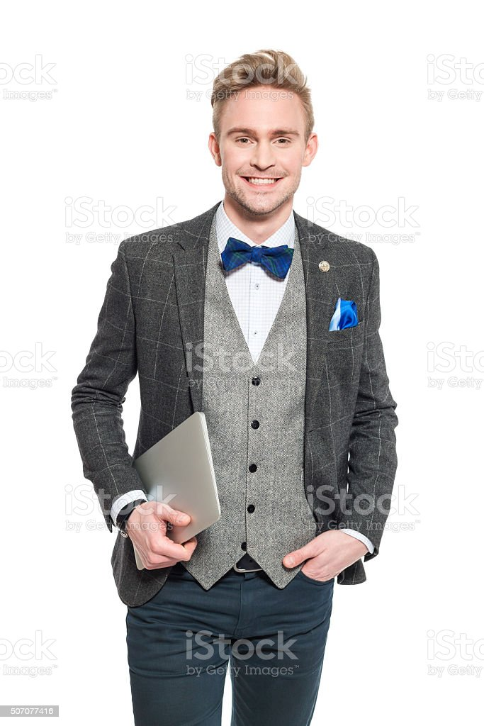 Fashionable young businessman in classical outfit, holding a digital tablet stock photo