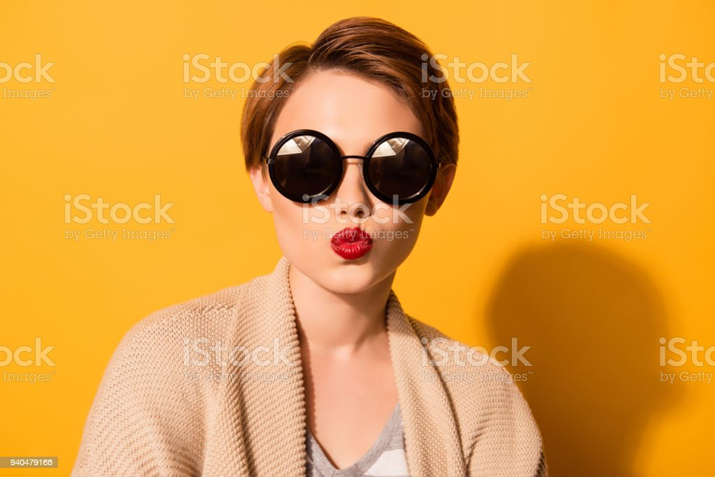 Fashionable young cute girl in trendy sunglasses sends a kiss  against bright yellow background stock photo