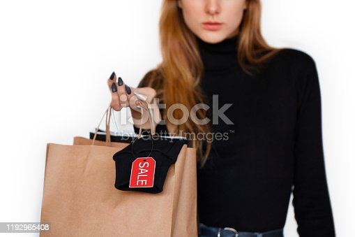 Concept of total sale on black friday. Cropped view of fashionable young girl standing in studio on white background with copy space, holding shopping bags in hands