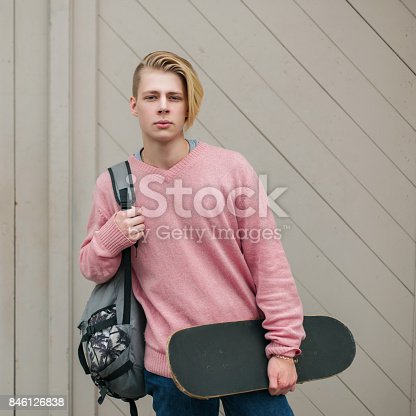 846124694 istock photo Fashionable young handsome man in a pink sweater with a backpack and skateboard near the wooden wall 846126838