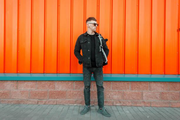 modieuze jonge hipster man met zonnebril in stijlvolle zwarte jeans kleding met een rugzak staat in de buurt van de oranje muur - zwarte spijkerbroek stockfoto's en -beelden