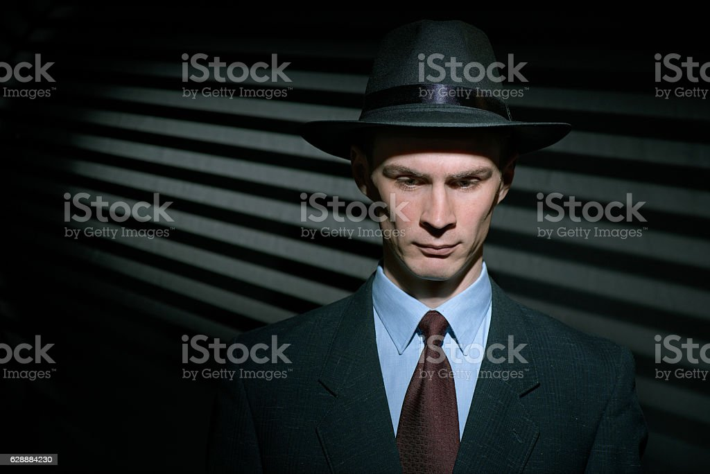 Fashionable young man detective in suit and trilby hat stock photo