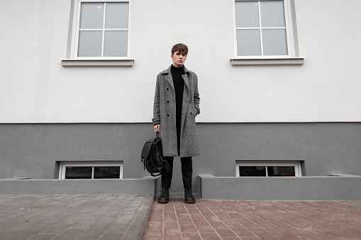 627398448 istock photo Fashionable young man in a gray elegant plaid coat with a leather stylish black backpack in autumn trendy boots stands near a vintage wall. Handsome modern guy in the city. Youth seasonal menswear. 1199258709