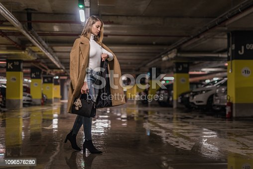 Fashionable young woman checking time in a public car garage.