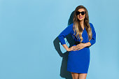 Beautiful young woman in blue mini dress and sunglasses is posing in the sunlight, holding hand on hip, looking away and smiling. Three quarter length studio shot on blue background.