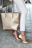 Fashionable young woman in elegant white paints and golden high heel shoes with handbag in hand on the city streets.