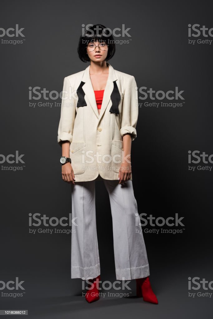 fashionable young woman in stylish jacket and bell-bottoms on grey stock photo
