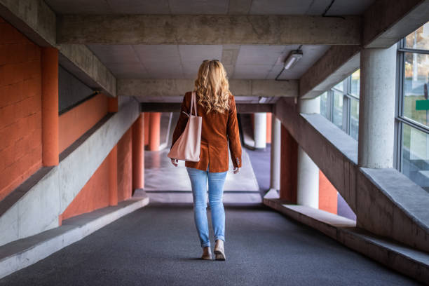 fashionable young woman walking in public car park. - corduroy stock pictures, royalty-free photos & images