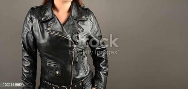 fashionable young women wearing bikers leather jacket isolated on gray with free space for your textual ideas.