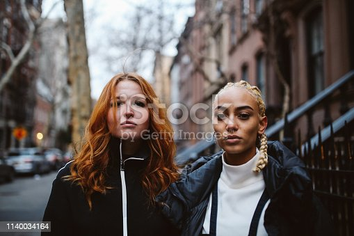 Vintage toned portrait of mixed ethnicity women from New York, standing on the street of Lower Manhattan, expressing street style youth culture attitude.