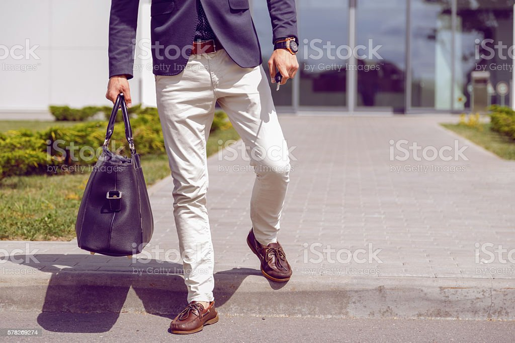 fashionably dressed businessman walks from office building with a bag stock photo