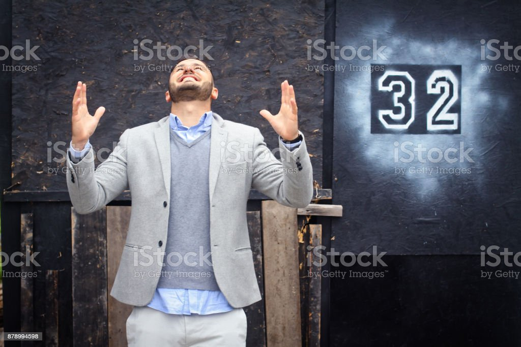 fashionably dressed man against the background of the graded wall. The guy and the old inscription 32. Creative photo for the design stock photo