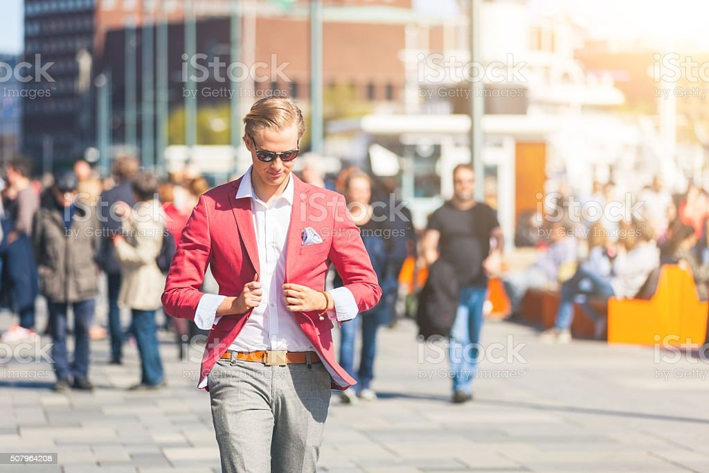 Fashioned young man in Oslo walking on crowded sidewalk stock photo