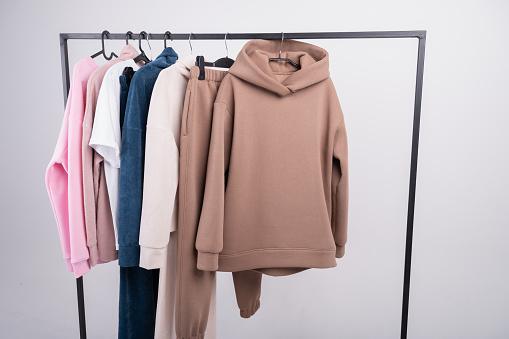 Fashionorange hoodie sweatshirt closeup with sweater and brown shirt on hanger background