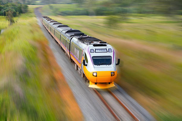 Fast aerodynamic diesel train blurred at speed Fast aerodynamic diesel train speeds through sub-tropical countryside.  The colourful train contrasts with its lush green surrounds. With motion blur.  All numbers and logos removed. Horizontal, copy space. bullet train stock pictures, royalty-free photos & images