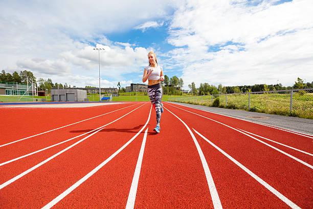 fast athletic female runner on outdoor running track - gewicht schnell verlieren stock-fotos und bilder