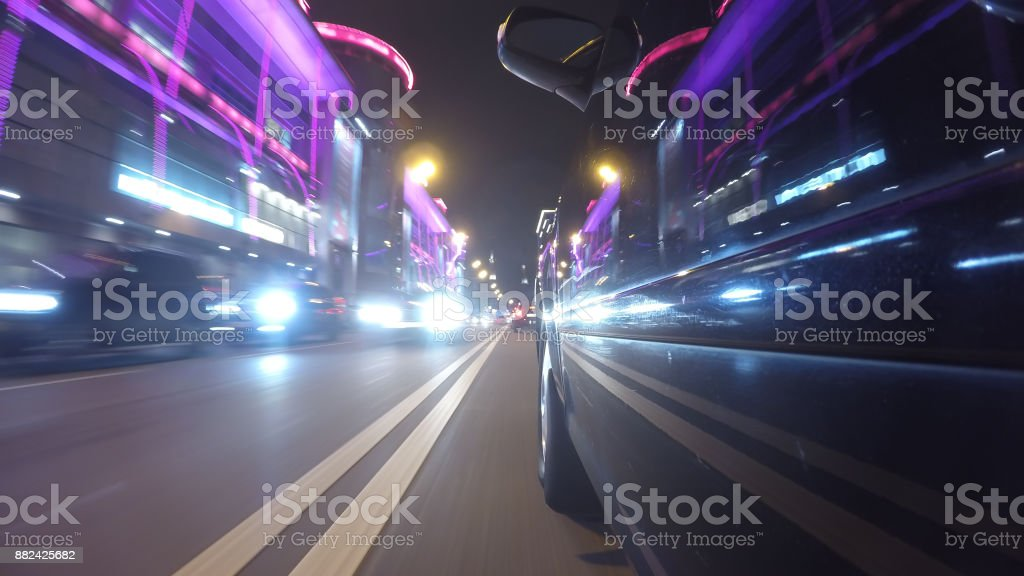 Fast city drive night road POV through city at night left side of car in blur. Reflection of city lights on car surface. Low angle view stock photo