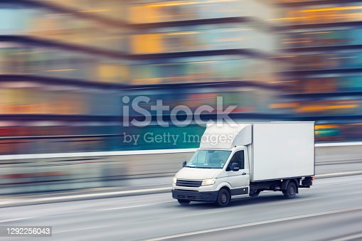A delivery truck travelling fast on a city street with motion blurred office buildings in the background.