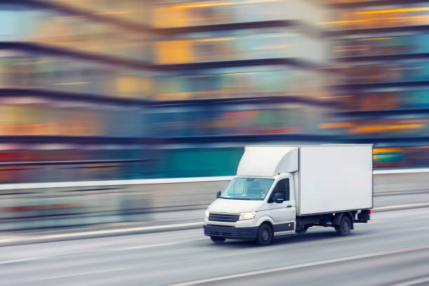 Fast delivery truck travelling through the city streets stock photo