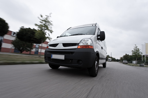 a white delivery van is speeding to its destination. motion blur on ground and wheels, vehicle is sharp.