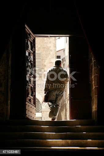 man leaving old building into bright sunshine