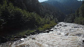 Fast flowing river. Dangerous rapids and big stones in the water. White seething water among the rocks.